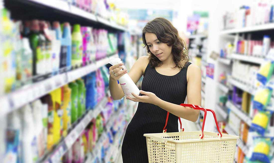 woman-reviewing-cleaning-product-in-supermarket